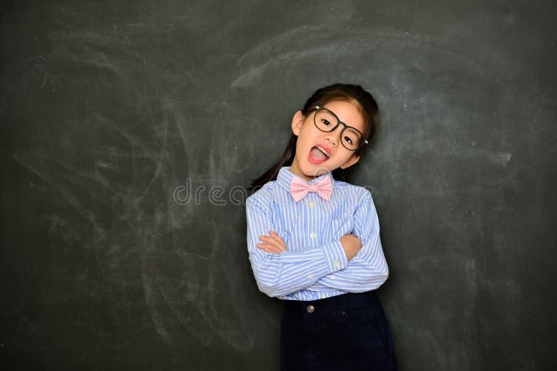 Счастливая маленькая девочка вручает пересеченный смотрящ камеру стоковая фотография