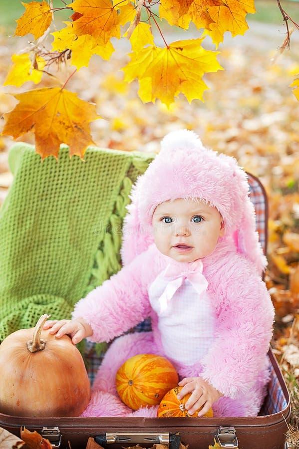 Счастливая маленькая девочка в костюме хеллоуина держа тыкву стоковое фото