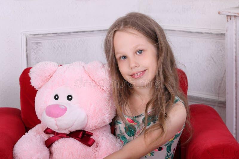 Счастливая маленькая девочка в платье сидит с большим медведем игрушки стоковые фотографии rf