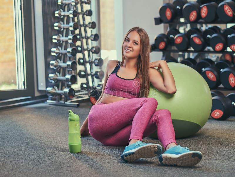 Счастливая маленькая девочка в розовом sportswear сидя на поле с шариком фитнеса и бутылкой воды на спортзале стоковая фотография
