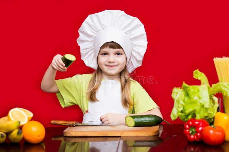 Счастливая маленькая девочка в форме шеф-повара режет овощи в кухне Шеф-повар ребенк стоковые фотографии rf