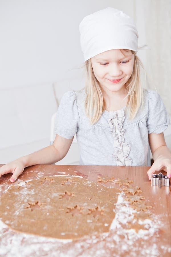 Счастливая маленькая девочка делая пряник стоковое изображение