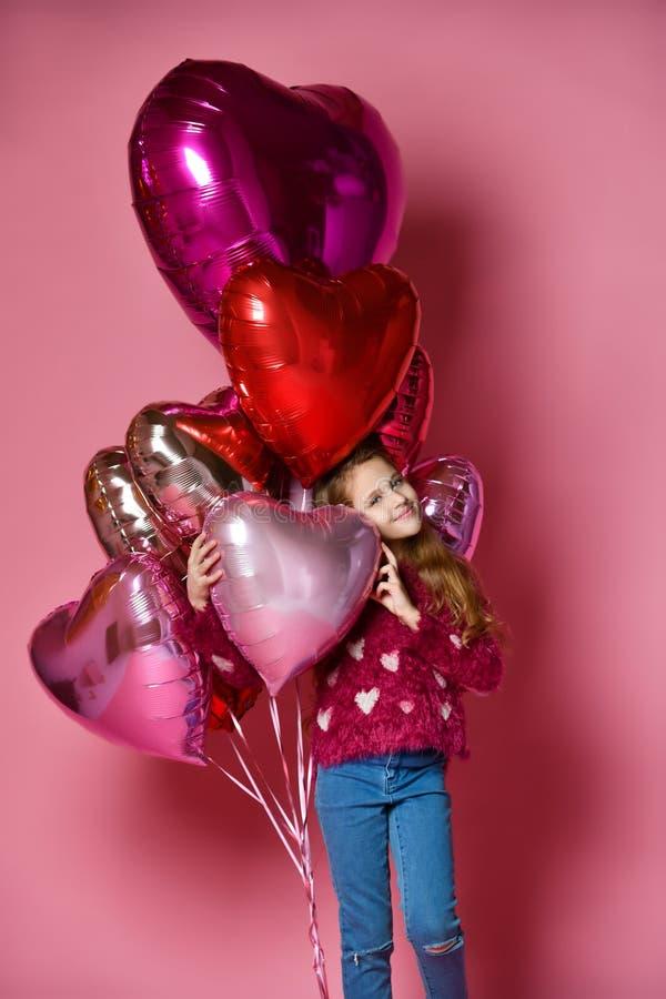 Счастливая маленькая девочка держа в форме сердц баллон стоковая фотография