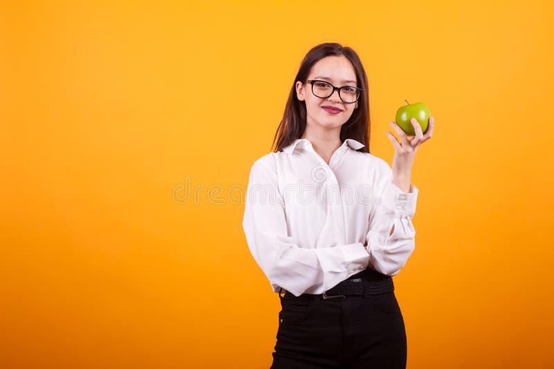 Счастливая маленькая девочка держа зеленое яблоко и усмехаясь к камере над желтой предпосылкой стоковое фото