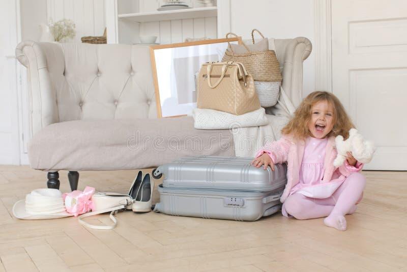 Счастливая маленькая девочка играя с ретро чемоданом стоковая фотография rf