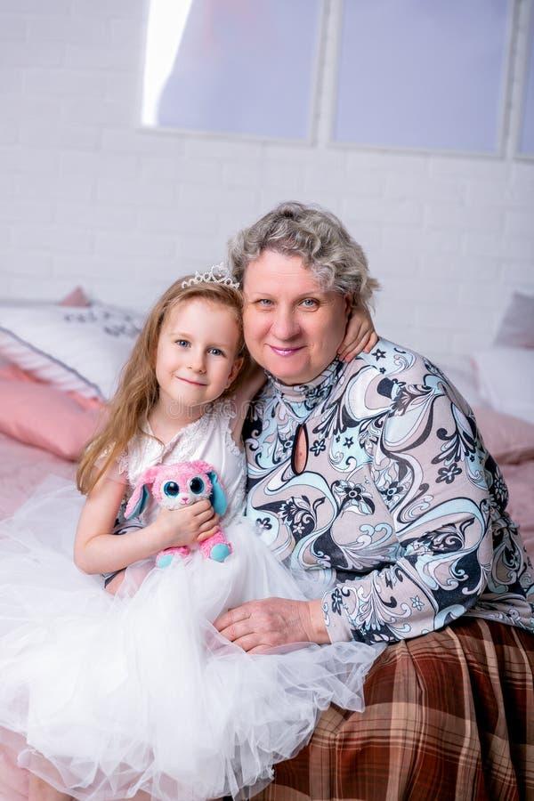 Счастливая маленькая девочка и ее бабушка сидят совместно и обнимают в спальне Они smilling и целуют Материнский стоковые фото