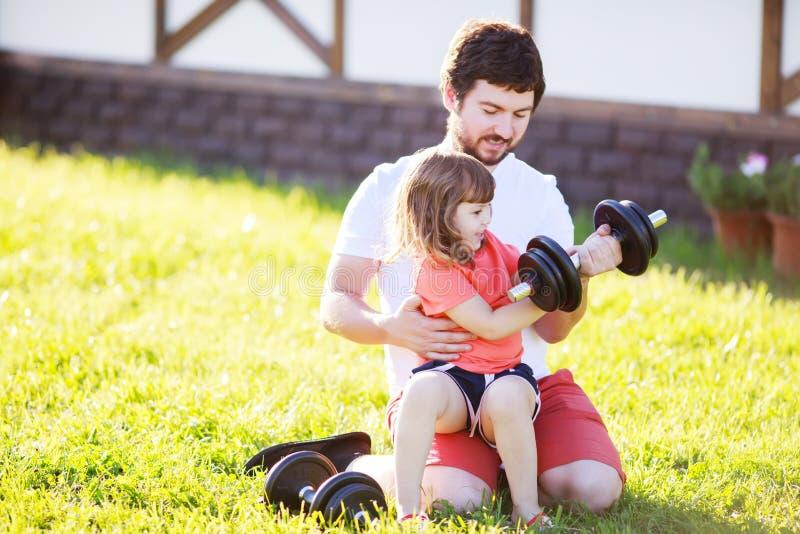 Счастливая маленькая девочка и ее гантели отца поднимаясь outdoors стоковые изображения rf