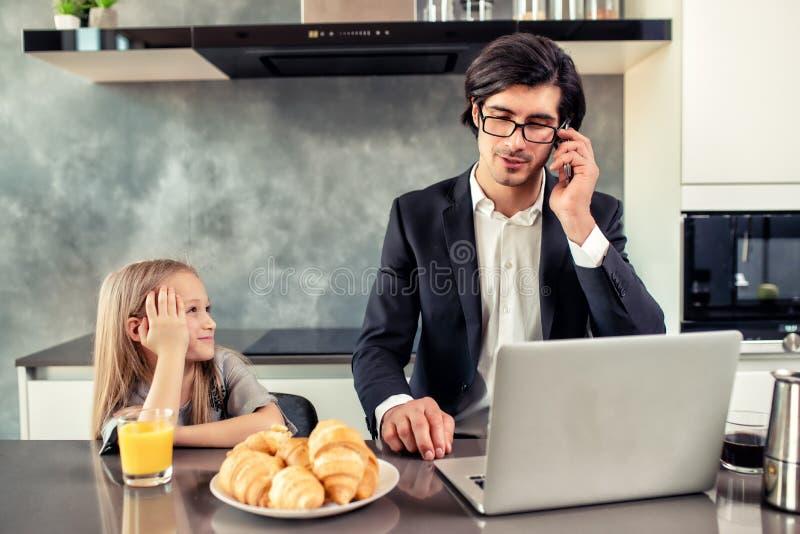 Счастливая маленькая девочка наблюдая его отца который работает стоковые изображения
