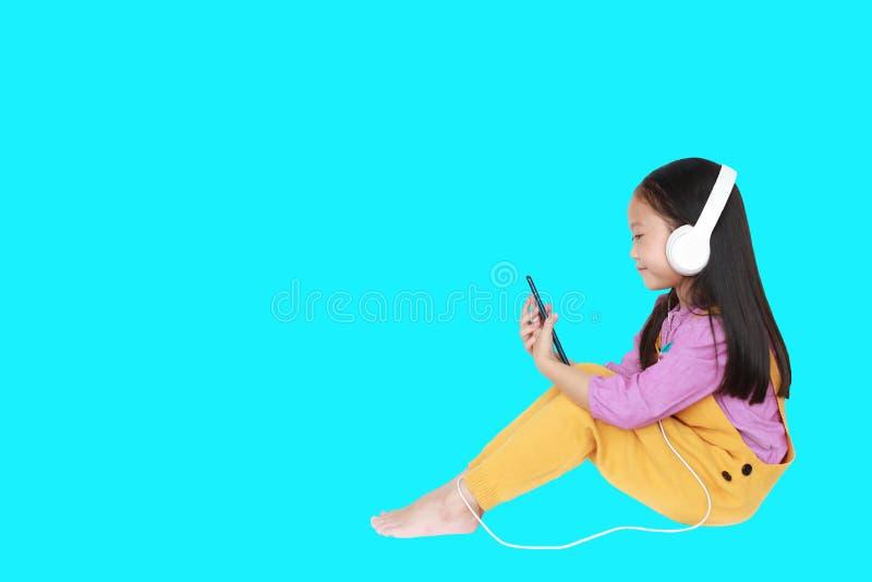 Счастливая маленькая девочка наслаждается слушать музыку с наушниками изолированными на cyan предпосылке с космосом экземпляра стоковое фото rf