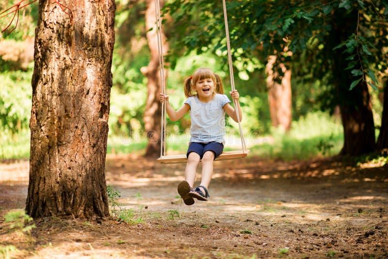 Счастливая маленькая девочка на качании в парке стоковое изображение