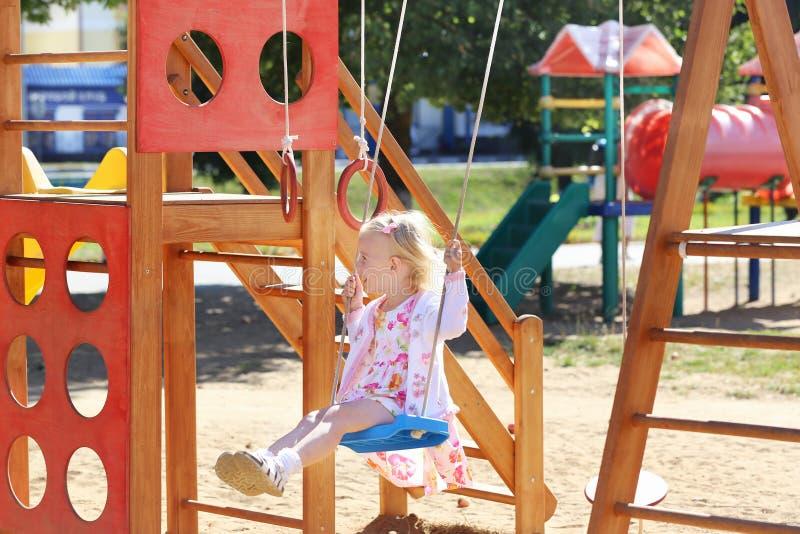 Счастливая маленькая девочка на спортивной площадке стоковое изображение rf