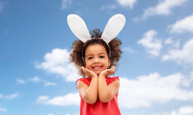Счастливая маленькая девочка нося представлять ушей зайчика пасхи стоковое изображение