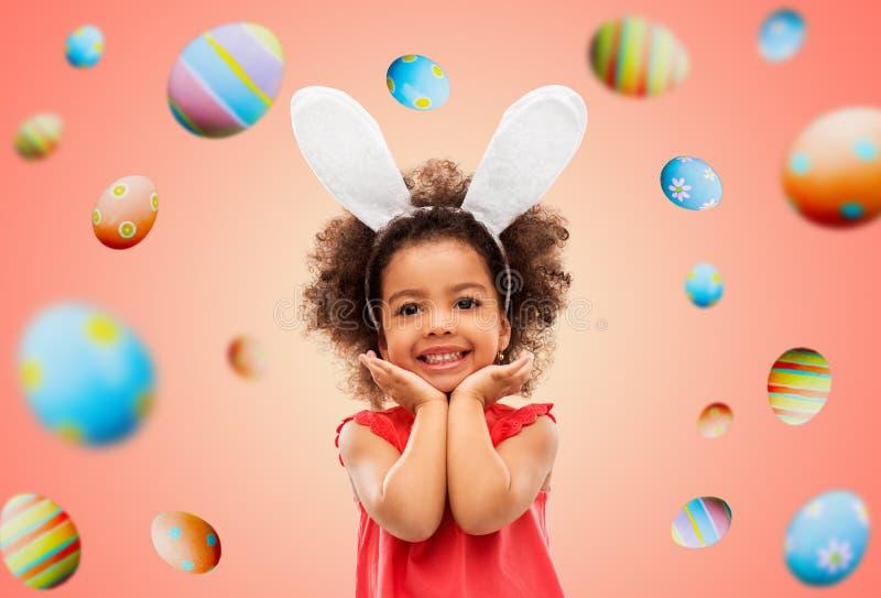 Счастливая маленькая девочка нося представлять ушей зайчика пасхи стоковое изображение rf