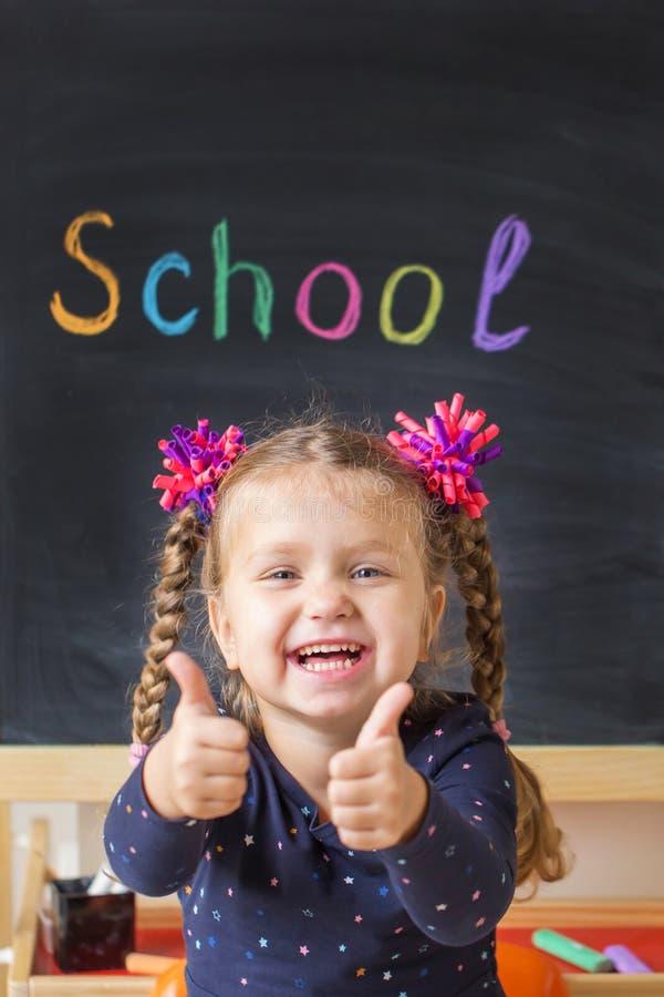 Счастливая маленькая девочка показывая знаки больших пальцев руки вверх на школьном правлении стоковые изображения rf