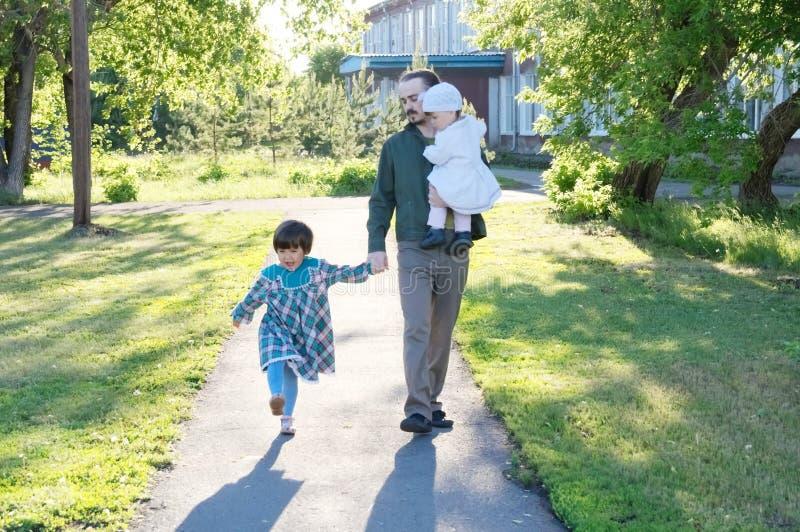 Счастливая маленькая девочка при отец идя в парк отец с 2 дочерьми на солнечном дне стоковое фото