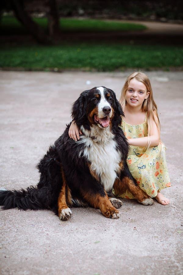 Счастливая маленькая девочка при собака стоя на дороге в парке Милая маленькая девочка обнимая собаку, усмехаясь Ребенок с собака стоковое фото