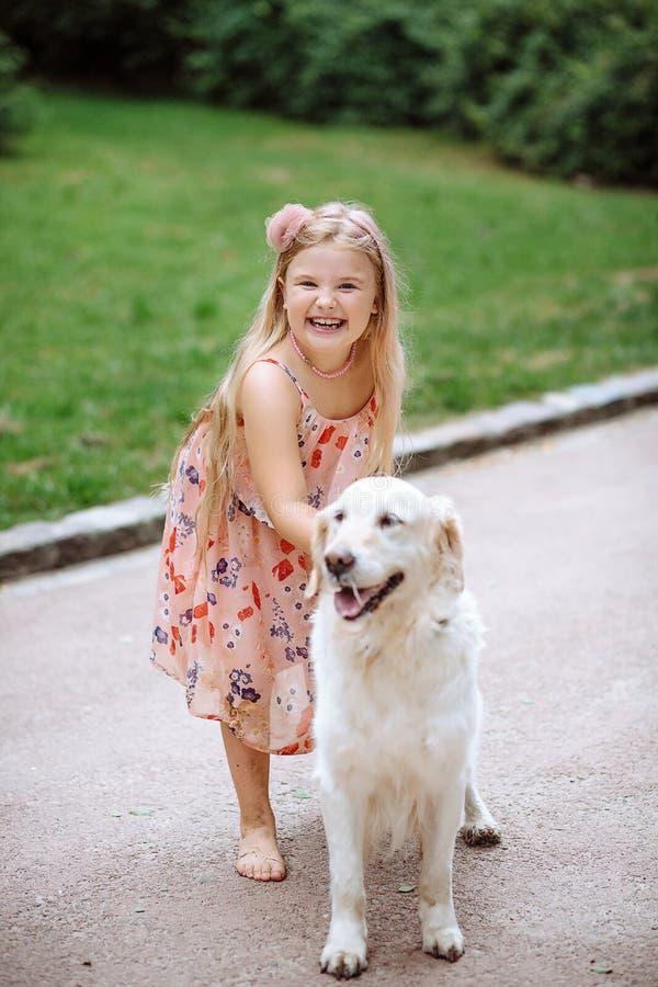 Счастливая маленькая девочка при собака стоя на дороге в парке Милая маленькая девочка обнимая собаку, усмехаясь Ребенок с собака стоковое фото rf
