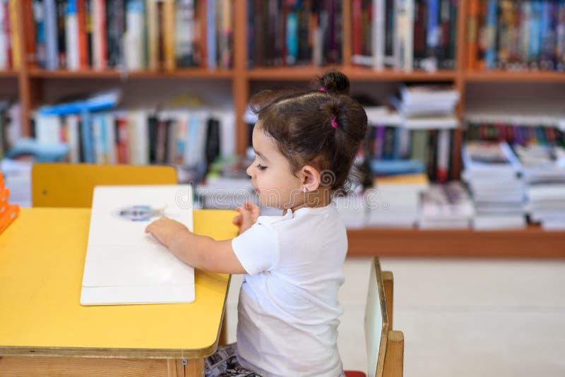 Счастливая маленькая девочка ребенка читая книгу стоковое изображение rf