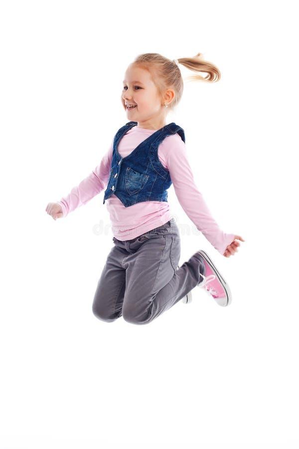 Счастливая маленькая девочка скача в воздух стоковое фото rf