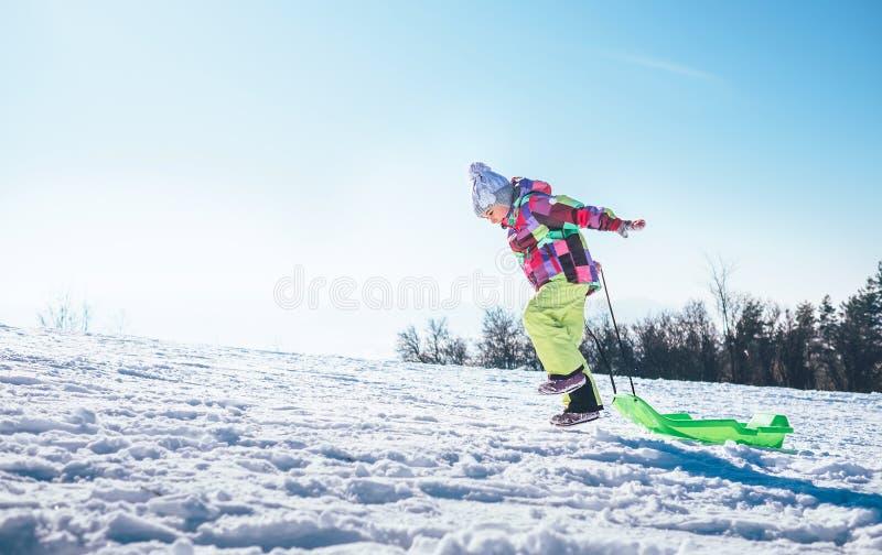 Счастливая маленькая девочка скачет вверх на наклон снега с яркой пластмассой стоковая фотография