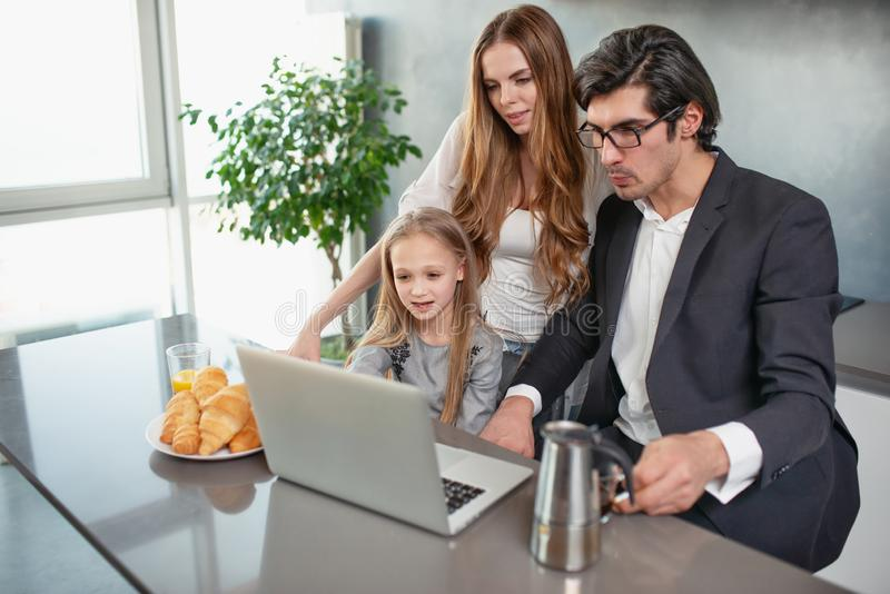 Счастливая маленькая девочка смотря фильм на компьютере с ее отцом и матерью стоковые изображения rf