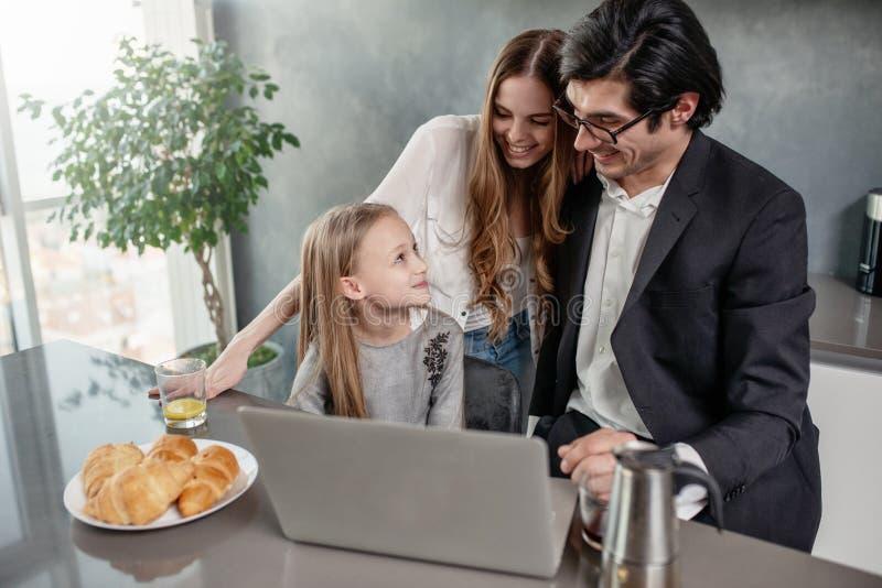 Счастливая маленькая девочка смотря фильм на компьютере с ее отцом и матерью стоковые фотографии rf