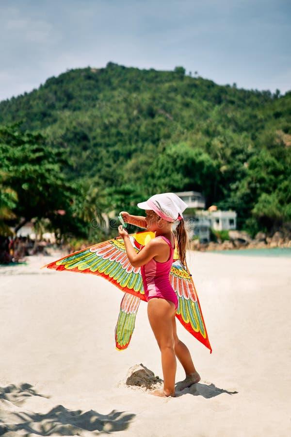 Счастливая маленькая девочка со змеем летания на тропическом пляже стоковые изображения rf