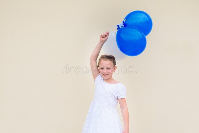 Счастливая маленькая девочка с голубыми и белыми воздушными шарами стоковые фотографии rf