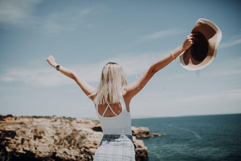 Счастливая маленькая девочка с соломенной шляпой стоит на максимуме и поднимает ее оружия вверх на виде на океан Призвание лета стоковые изображения