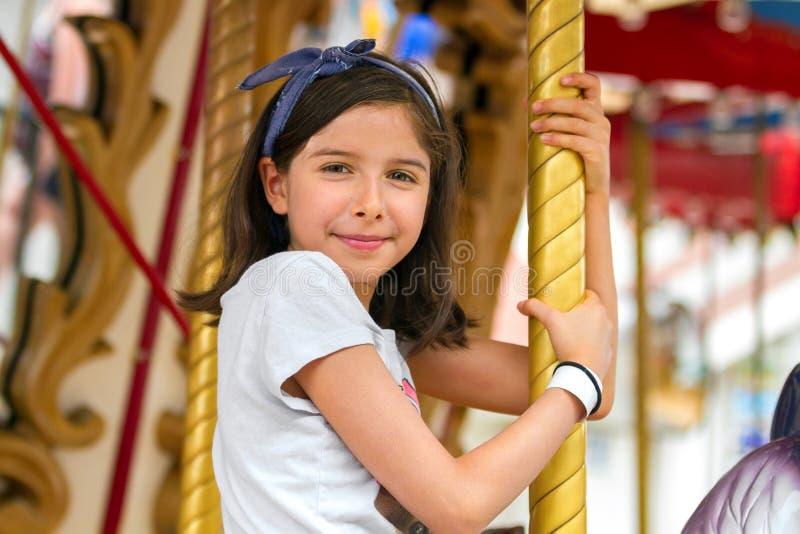 Счастливая маленькая девочка усмехаясь конфиденциально пока сидящ на Carous стоковое фото rf