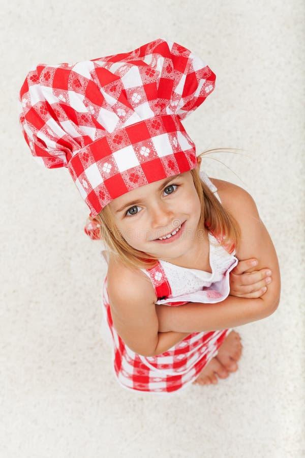 Счастливая маленькая девушка шеф-повара смотря вверх и усмехаясь стоковое фото