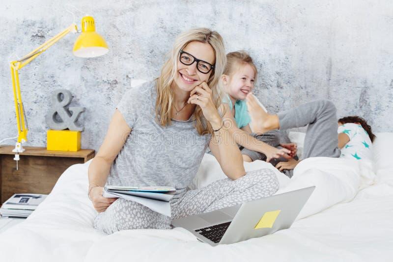 Счастливая мама дела на работе пока ее дети играют в кровати стоковые изображения