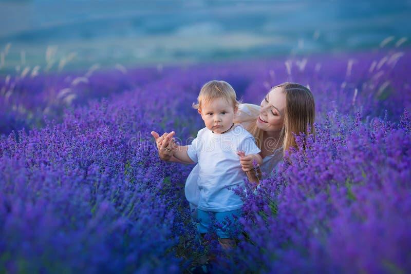 Счастливая мама с милым сыном на предпосылке лаванды Красивые женщина и мальчик в поле луга Ландшафт лаванды с дамой и ребенк стоковые изображения