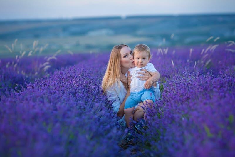 Счастливая мама с милым сыном на предпосылке лаванды Красивые женщина и мальчик в поле луга Ландшафт лаванды с дамой и ребенк стоковая фотография rf