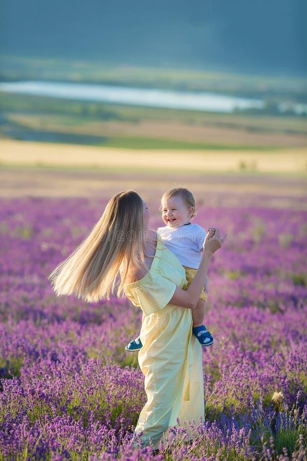 Счастливая мама с милым сыном на предпосылке лаванды Красивые женщина и мальчик в поле луга Ландшафт лаванды с дамой и ребенк стоковая фотография