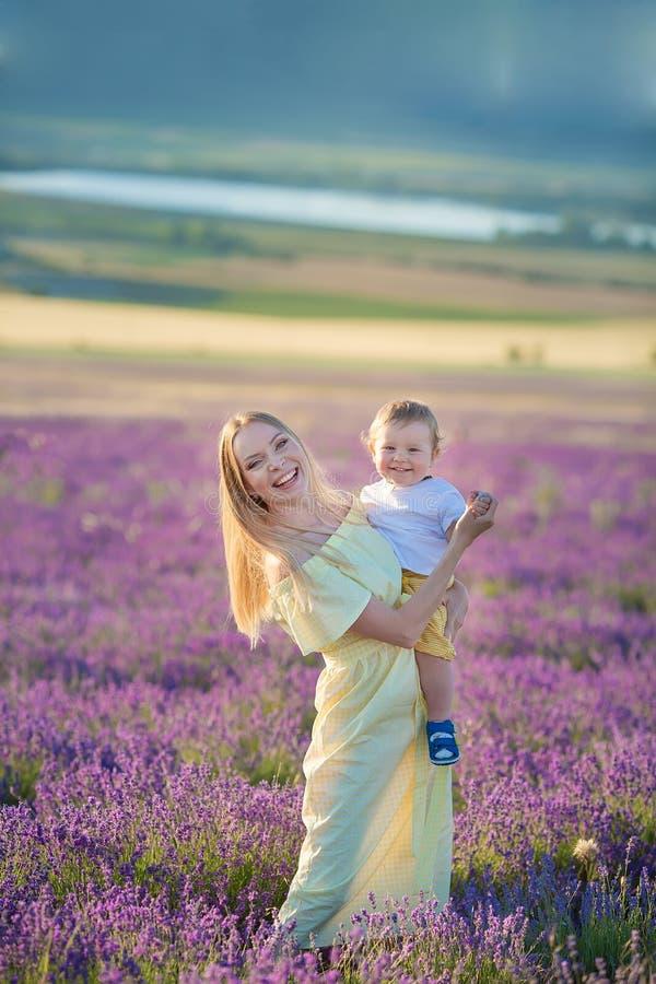 Счастливая мама с милым сыном на предпосылке лаванды Красивые женщина и мальчик в поле луга Ландшафт лаванды с дамой и ребенк стоковое изображение rf