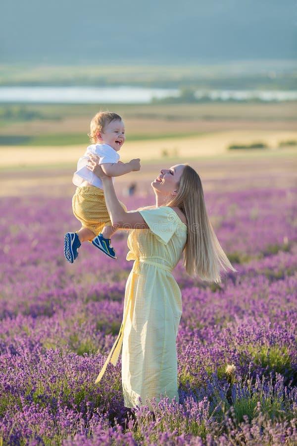 Счастливая мама с милым сыном на предпосылке лаванды Красивые женщина и мальчик в поле луга Ландшафт лаванды с дамой и ребенк стоковые фото