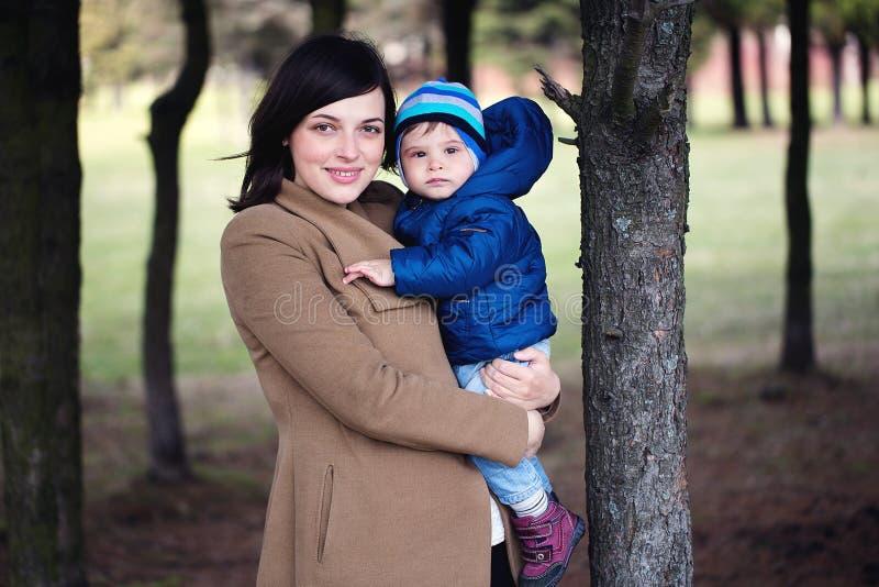 Счастливая мать держа ее маленького сына в ее оружиях в парке девушка  стоковое фото rf