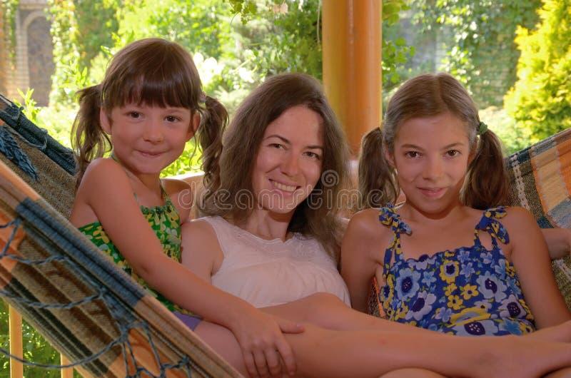 Счастливая мать и дети имея потеху в гамаке стоковое изображение