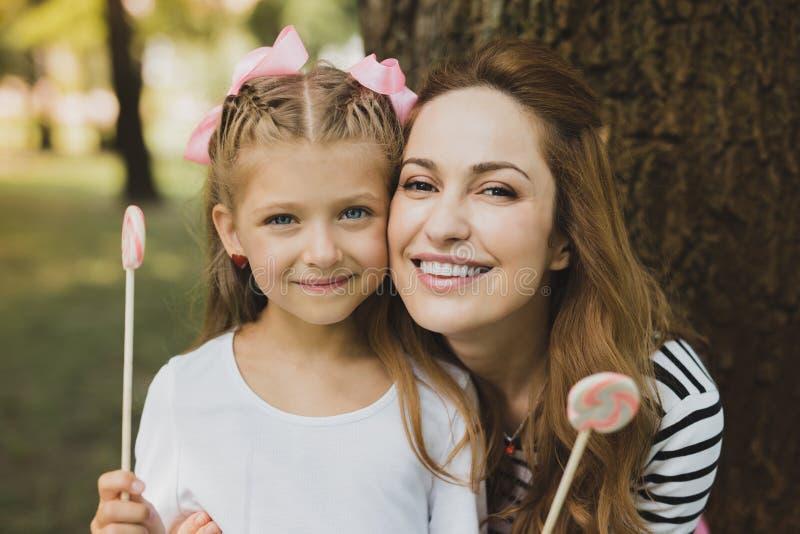 Счастливая мать и дочь есть сладостные леденцы на палочке на празднике стоковые изображения rf