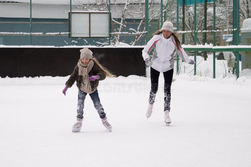 Счастливая мать и дочь катаясь на коньках на на открытом воздухе катке стоковое фото rf