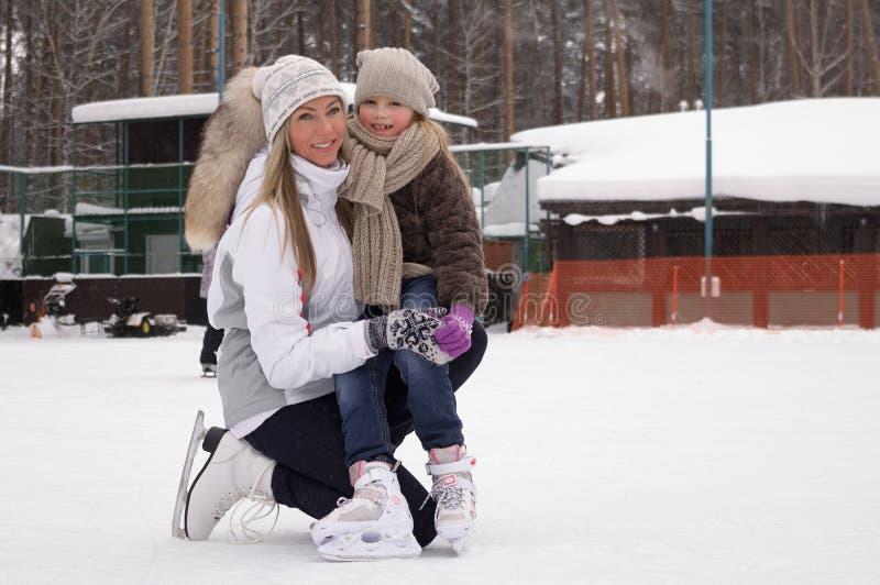 Счастливая мать и дочь катаясь на коньках на на открытом воздухе катке стоковое изображение rf
