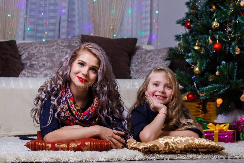 Счастливая мать и дочь, представляя против настроения рождественской елки, рождества и Нового Года, конца-вверх стоковые изображения