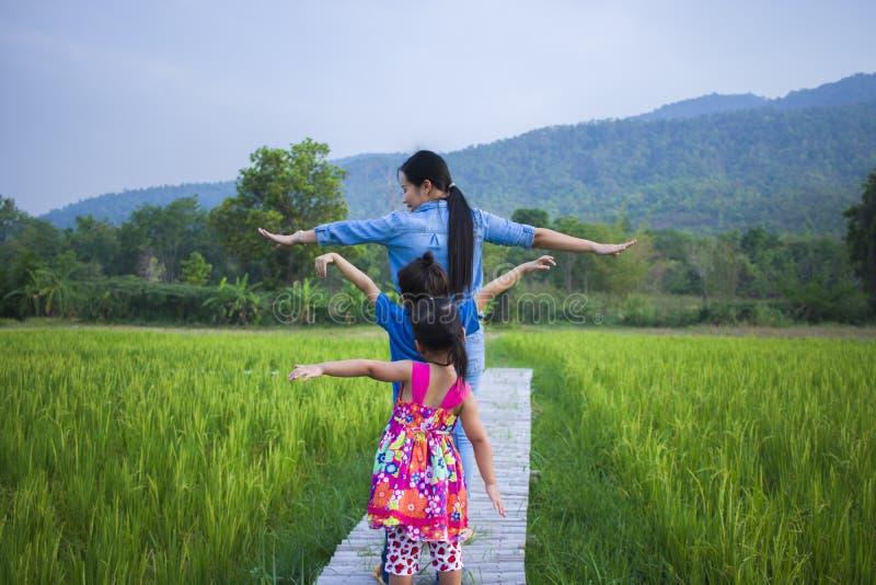 Счастливая мать и ее детская игра outdoors имея потеху, землю зеленого поля риса заднюю стоковое изображение