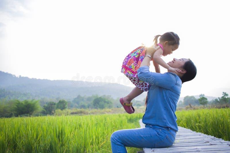 Счастливая мать и ее детская игра outdoors имея потеху, землю зеленого поля риса заднюю стоковые изображения rf
