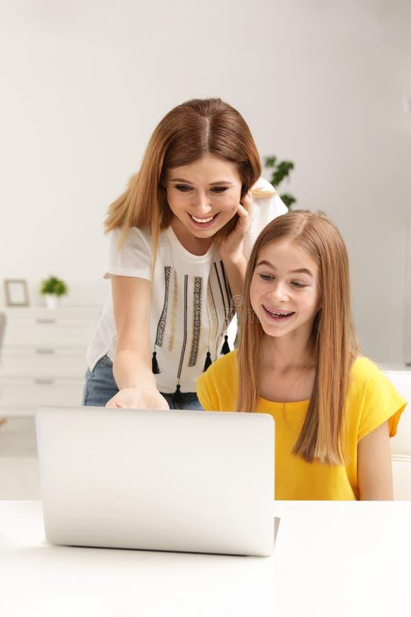 Счастливая мать и ее дочь подростка с ноутбуком стоковое изображение rf