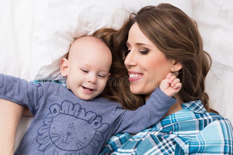Счастливая мать и ее сын младенца лежа на кровати совместно семья счастливая мать ребенка newborn стоковая фотография