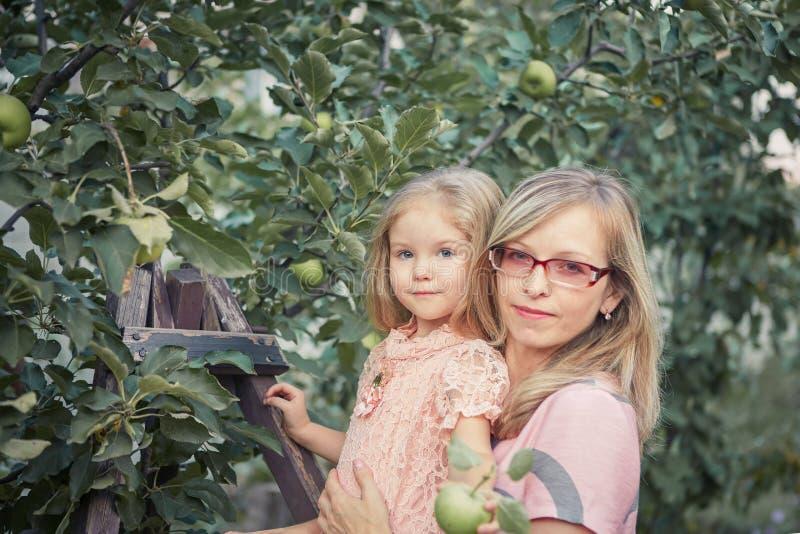 Счастливая мать и маленькие яблоки рудоразборки дочери в саде стоковое изображение rf