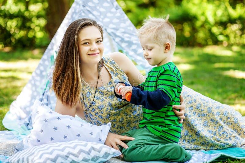 Счастливая мать и маленький сын играя в парке Пузыри Co стоковая фотография