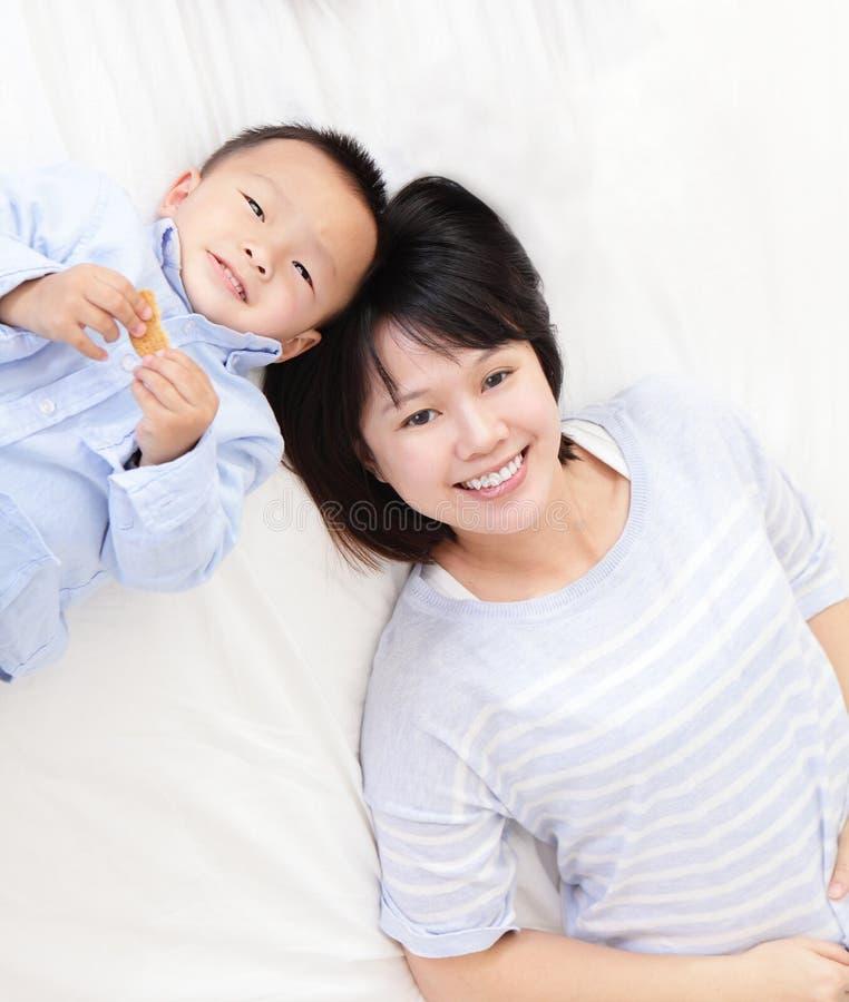 Счастливая мать и сынок лежа на кровати стоковое фото rf